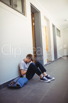 Sad schoolboy sitting in corridor