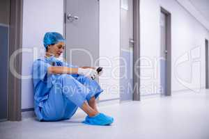 Surgeon sitting on floor and using mobile phone