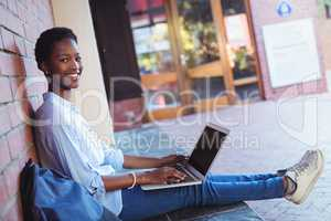 Portrait of happy schoolgirl sitting against brick wall and using laptop