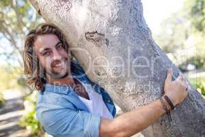 Portrait of man hugging a tree trunk in park