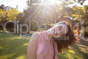 Portrait of beautiful woman swaying her hair in the park