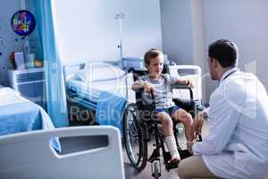 Male doctor interacting with child patient in ward