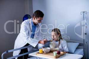 Doctor feeding breakfast to patient