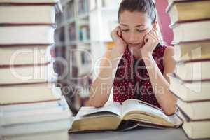 Attentive schoolgirl studying in library