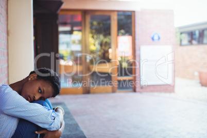 Sad schoolgirl sitting in school campus