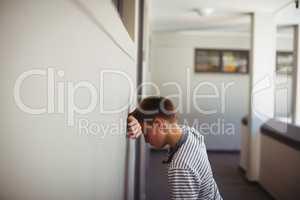 Sad schoolboy leaning head against wall in corridor