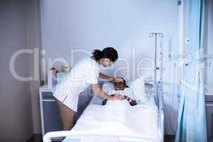 Female doctor checking patient fever in ward