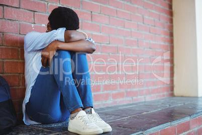 Sad schoolgirl sitting against brick wall