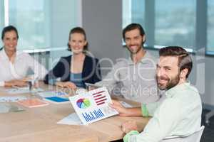 Smiling business executives sitting together in conference room with graph