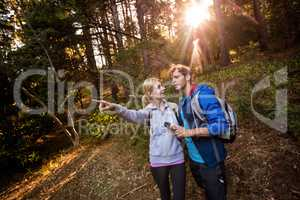 Hiking couple holding a compass and pointing forward