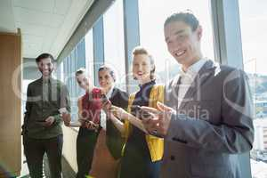 Business executives smiling while using electronic devices