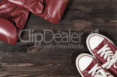 Red boxing gloves and red sneakers on a wooden surface