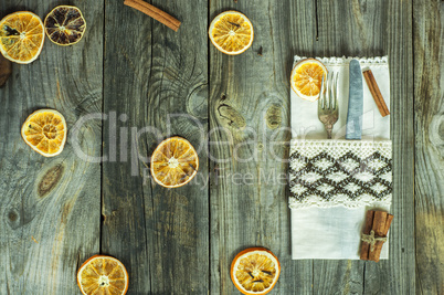 Table knife and fork on gray wooden surface with slices of dried