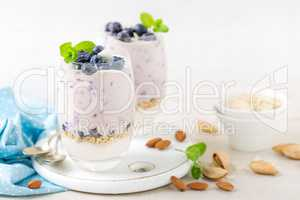 Greek yogurt or blueberry parfait with fresh berries and almond nuts on white background, healthy eating