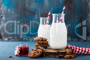 Milk in glass bottle on blue background, breakfast