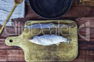 Frozen fish smelt on the kitchen board