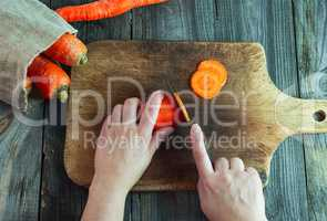 process of slicing carrots on slices on a kitchen board