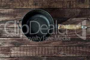 Black cast-iron frying pan on a brown wooden surface