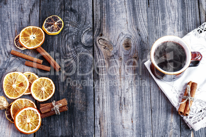 cup of hot coffee with orange slices on a gray wooden surface