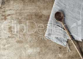 Brown wooden background with a wooden spoon and a gray tableclot