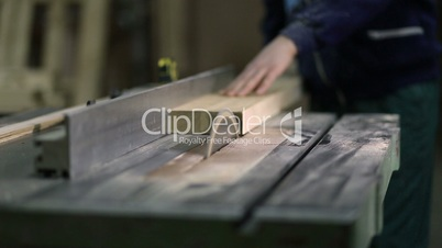 Carpenter working on electric saw cutting boards