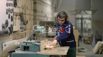 Craftsman cutting wooden plank with circular saw