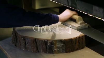 Carpenter sanding log slice with band grinder