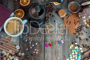 cup of black coffee with sweets and spices on a gray wooden surf