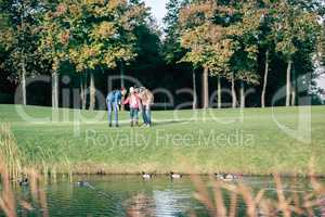 Happy family looking at ducks in park