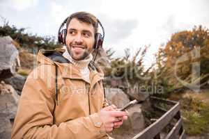 Man in headphones holding smartphone