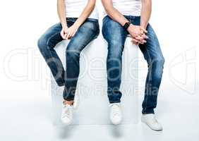 Couple sitting in jeans and white shoes