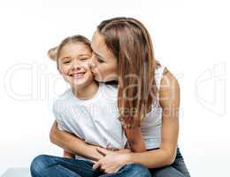 Mother hugging and kissing smiling daughter
