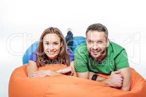 Smiling couple lying in sack-chair