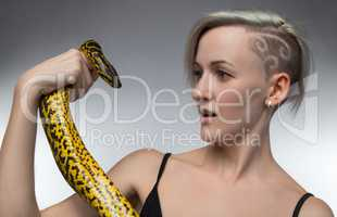 Young woman holding yellow snake