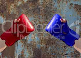 Two female hands in red and blue boxing gloves