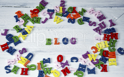 Word blog of small multicolored letters on a white surface