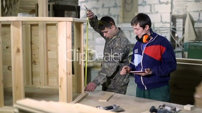 Carpenters using digital tablet in workshop