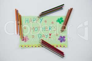 Color pencil arranged around mothers day greetings card