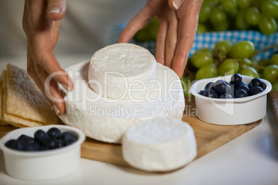 Hands of female staff arranging cheese at counter