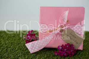 Gift box with happy mother day tag and flowers on grass