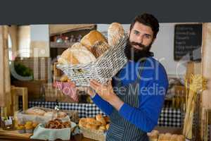 Portrait of male staff carrying wicker basket of breads at counter