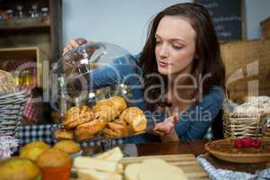 Woman buying croissant at bakery counter