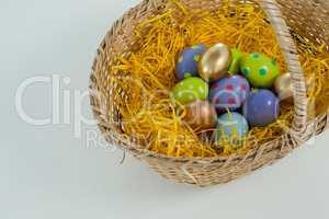 Various Easter eggs in wicker basket