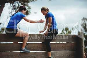Female trainer assisting woman to climb a wooden wall