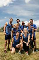 Group of fit people posing together in boot camp