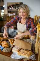 Smiling female staff packing doughnut in paper bag at counter