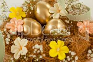 Golden easter eggs with flowers in nest