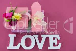 Gift boxes with flowers and text love against pink background
