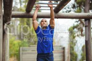 Fit man climbing monkey bars