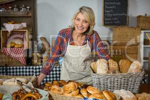 Portrait of smiling female staff standing at bread counter